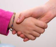 Mãos entrelaçadas das meninas, toque das mãos Fotografia de Stock Royalty Free