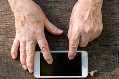 Mãos envelhecidas usando o tela táctil de um móbil Imagens de Stock Royalty Free
