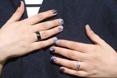Mãos fêmeas bonitas com tratamento de mãos extraordinário Projeto criativo do prego no azul Cores ultra à moda do verniz para as  Fotografia de Stock