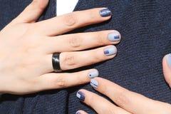 Mãos fêmeas bonitas com tratamento de mãos extraordinário Projeto criativo do prego no azul Cores ultra à moda do verniz para as  Imagens de Stock