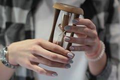 Mãos fêmeas bonitas com tratamento de mãos para guardar uma ampulheta Beleza e conceito da forma imagem de stock royalty free