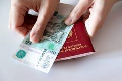 Mãos fêmeas colhidas que guardam o passaporte do russo e o papel moeda internacionais, rublos imagem de stock