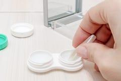 Mãos fêmeas colhidas que tomam lentes de contato fora de um recipiente imagens de stock