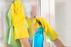 Mãos fêmeas com as luvas protetoras amarelas que limpam a janela em casa que usa o pulverizador verde de pano e de detergente Fotografia de Stock