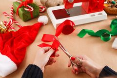 Mãos fêmeas com as tesouras que cortam a fita vermelha Xmas diy Foto de Stock