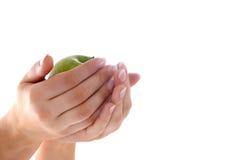 Mãos fêmeas com manicure e a maçã agradáveis Foto de Stock Royalty Free