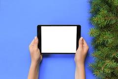 Mãos fêmeas com o tablet pc no fundo roxo do Natal Opinião superior de ramo de árvore do Xmas foto de stock royalty free