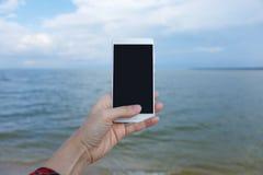 Mãos fêmeas com o telefone esperto que toma imagens do mar imagens de stock