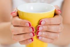 Mãos fêmeas com o verniz de prego que guarda a caneca Foto de Stock