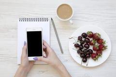 Mãos fêmeas com smartphone, latte, caderno, morangos e cerejas no fundo de madeira branco, vista superior Imagem de Stock