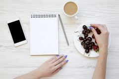 Mãos fêmeas com smartphone, latte, caderno, morangos e cerejas no fundo de madeira branco, vista superior Configuração lisa Imagem de Stock