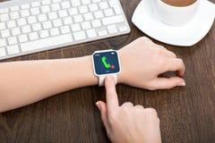 Mãos fêmeas com smartwatch com telefonema imagens de stock