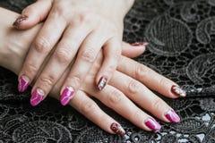 Mãos fêmeas com tratamento de mãos bonito em um fundo preto com laço foto de stock