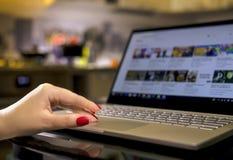 Mãos fêmeas com tratamento de mãos brilhante em um teclado do portátil na noite em casa foto de stock