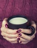 Mãos fêmeas com um copo do leite morno fotografia de stock royalty free