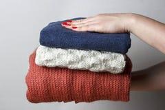 Mãos fêmeas com um tratamento de mãos vermelho que guarda uma pilha de coisas de lã feitas malha, vista dianteira, close-up imagem de stock royalty free