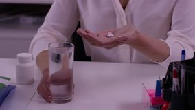 Mãos fêmeas com vidro da água e das tabuletas Mão da mulher com as tabuletas da medicina dos comprimidos e o vidro da água para a vídeos de arquivo