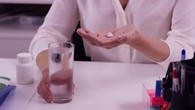 Mãos fêmeas com vidro da água e das tabuletas Mão da mulher com as tabuletas da medicina dos comprimidos e o vidro da água para a fotos de stock