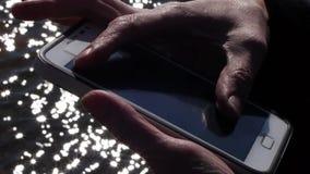 Mãos fêmeas das imagens de vídeo conservadas em estoque que trabalham com um smartphone video estoque
