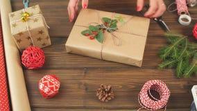 Mãos fêmeas do close up que decoram caixas vermelhas do presente para o feriado do Natal Ideias de empacotamento atuais filme