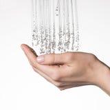 Mãos fêmeas do close up sob o córrego de espirrar a água Foto de Stock
