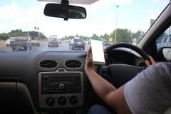 Mãos fêmeas do motorista que guardam o painel da direção do carro com o telefone esperto da placa da terra arrendada na estrada imagens de stock royalty free