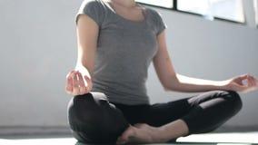 Mãos fêmeas durante a meditação da ioga na pose dos lótus no movimento lento rápido do estúdio video estoque