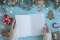 Mãos fêmeas em uma camiseta branca para manter um cartão de Natal em um fundo azul fotos de stock royalty free