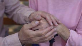 Mãos fêmeas envelhecidas da coberta masculina, cuidado de lar de idosos, apoio da família, auxílio video estoque