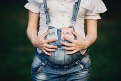 Mãos fêmeas na barriga com com os cartões do MENINO e da MENINA fotos de stock