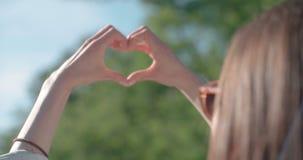 Mãos fêmeas na forma do coração sobre a natureza verde e o céu azul vídeos de arquivo