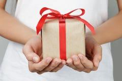 Mãos fêmeas novas que guardaram o presente Imagem de Stock Royalty Free