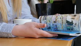 Mãos fêmeas novas que lançam através de um compartimento de forma que senta-se no café imagem de stock royalty free