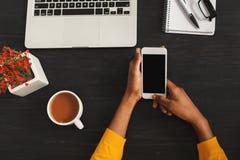 Mãos fêmeas pretas que guardam o smartphone, vista superior imagem de stock