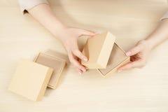 Mãos fêmeas que abrem a caixa da caixa, configuração do plano Imagens de Stock Royalty Free