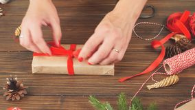 Mãos fêmeas que amarram uma curva com a fita vermelha no giftbox, envolvido no papel do ofício video estoque