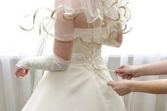 Mãos fêmeas que apertam um espartilho à noiva Imagem de Stock