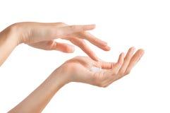 Mãos fêmeas que aplicam o moisturiser fotografia de stock