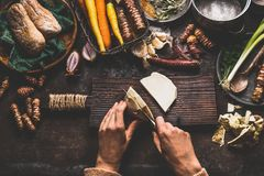 Mãos fêmeas que cortam o aipo no fundo rústico escuro da mesa de cozinha com os vários vegetais e utensílios Cozimento dos vegeta Fotos de Stock