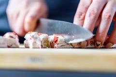 Mãos fêmeas que cortam o fruto da morango e o nougat da porca com a faca na placa de madeira Fotografia de Stock Royalty Free