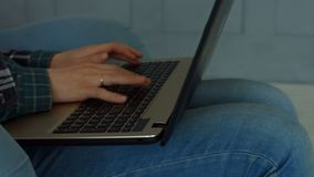 Mãos fêmeas que datilografam no teclado do portátil em casa filme