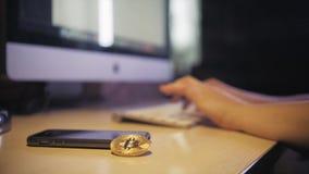 Mãos fêmeas que datilografam no teclado Suportes do bitcoin da moeda verticalmente na tabela vídeos de arquivo