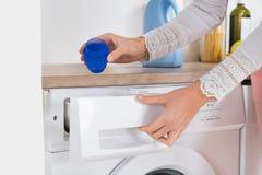 Mãos fêmeas que derramam o detergente na máquina de lavar Fotos de Stock