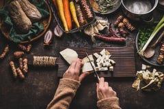 Mãos fêmeas que desbastam o aipo no fundo rústico escuro da mesa de cozinha com os vários vegetais e utensílios Cozimento dos veg Fotos de Stock