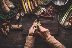 Mãos fêmeas que descascam o aipo no fundo rústico escuro da mesa de cozinha com os vários vegetais e utensílios Cozimento dos veg Imagem de Stock