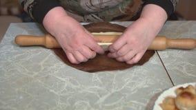 Mãos fêmeas que desenrolam a massa com um pino do rolo em uma tabela clara video estoque