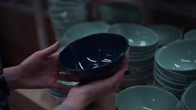 Mãos fêmeas que escolhem placas na seção do dishware na loja dos eletrodomésticos vídeos de arquivo