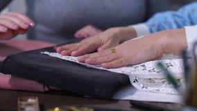 Mãos fêmeas que escolhem telas em costurar a oficina filme