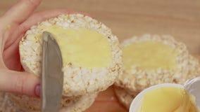 Mãos fêmeas que espalham o queijo creme no pão video estoque