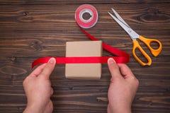 Mãos fêmeas que fazem da caixa de presente feito a mão com fita e o sci vermelhos Imagem de Stock Royalty Free